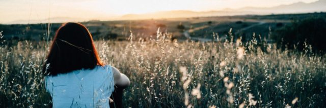 young woman sitting among flowers and grass watching sunrise alone