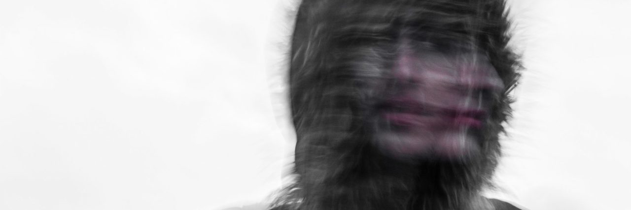 distorted double exposure image of woman looking two directions at once wearing hood