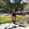 a woman stands in a garden of flowers