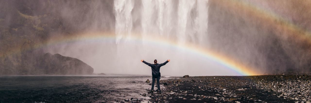 person standing in front of a waterfall with a rainbow overhead