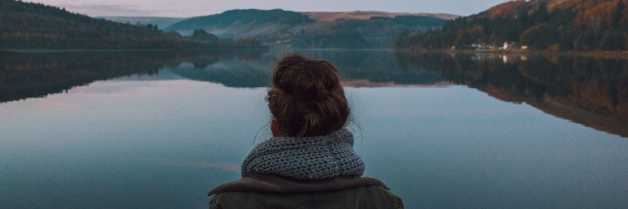 woman standing alone in front of still lake surrounded by mountains