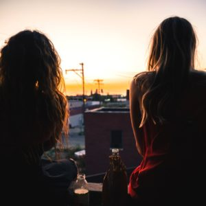two young women watching sunset together back view