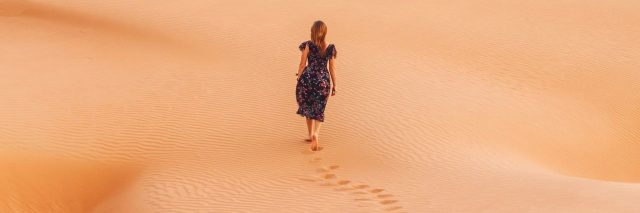 woman walking through desert leaving footprints behind