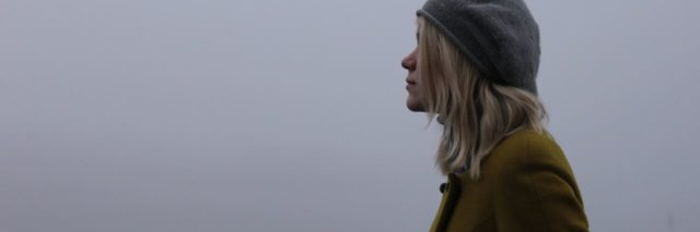 blonde woman standing in profile in mist