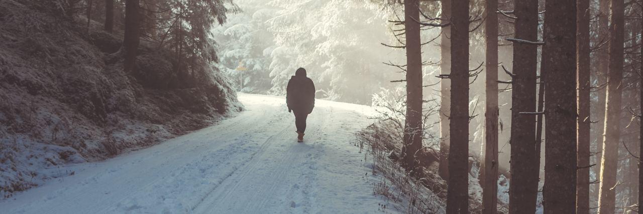 person walks down snowy street alone in the winter