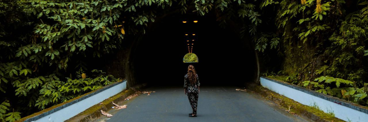 woman stands in front of a bridge covered in vines