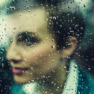 soft focus of woman with focus on raindrops on window
