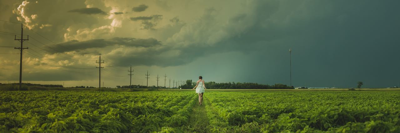 woman in field looking at storm on horizon