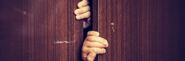 Hands pulling open closet doors.