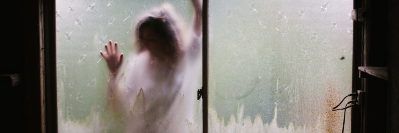 woman on other side of frosted window pressed against glass