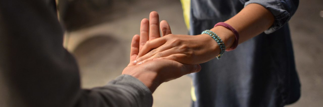 two people holding hands help gesture