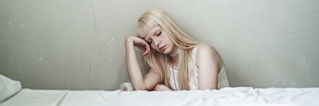 blonde woman sitting beside bed depressed against white wall