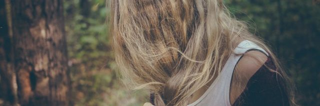 blonde woman with hair hiding face in woods looking anxious or upset