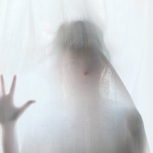 woman stands behind curtain with hand pressed to curtain