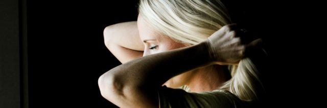 woman stands pulling her hair back