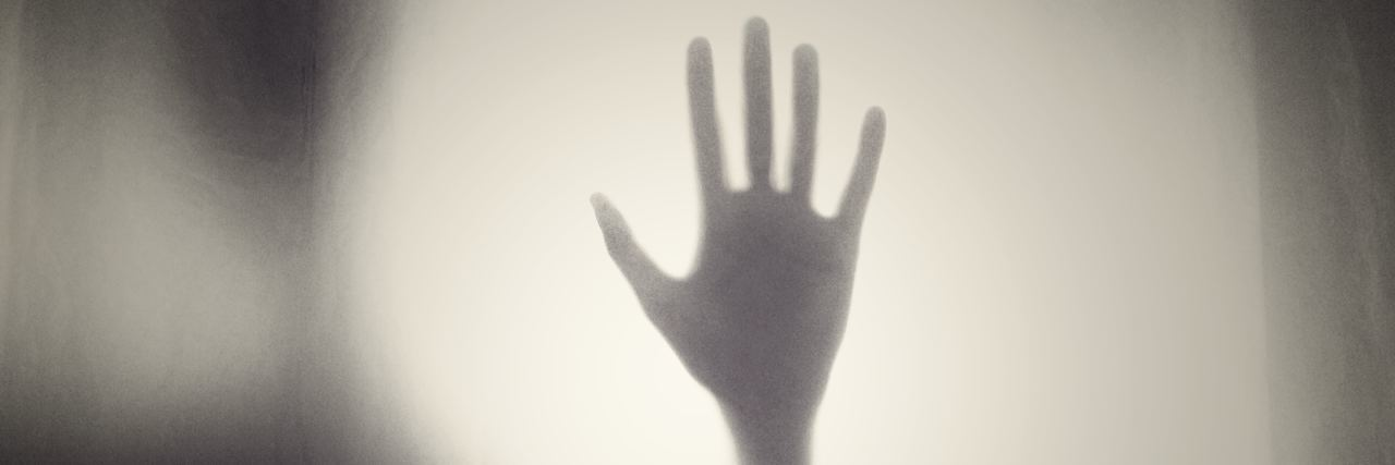 a hand pressed against a foggy pane of glass