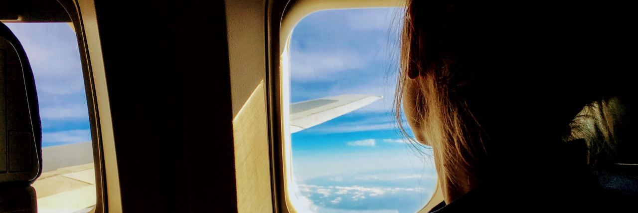 woman looking out a plane window watching the clouds