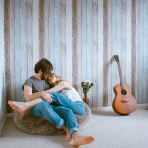 man and woman cuddled on bean bag next to acoustic guitar
