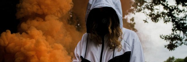 person stands with their head down in a cloud of smoke