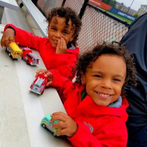 Twins smiling at camera wearing matching red coats