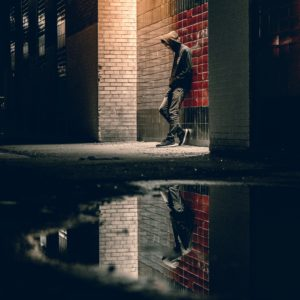 man standing alone against wall on dark street