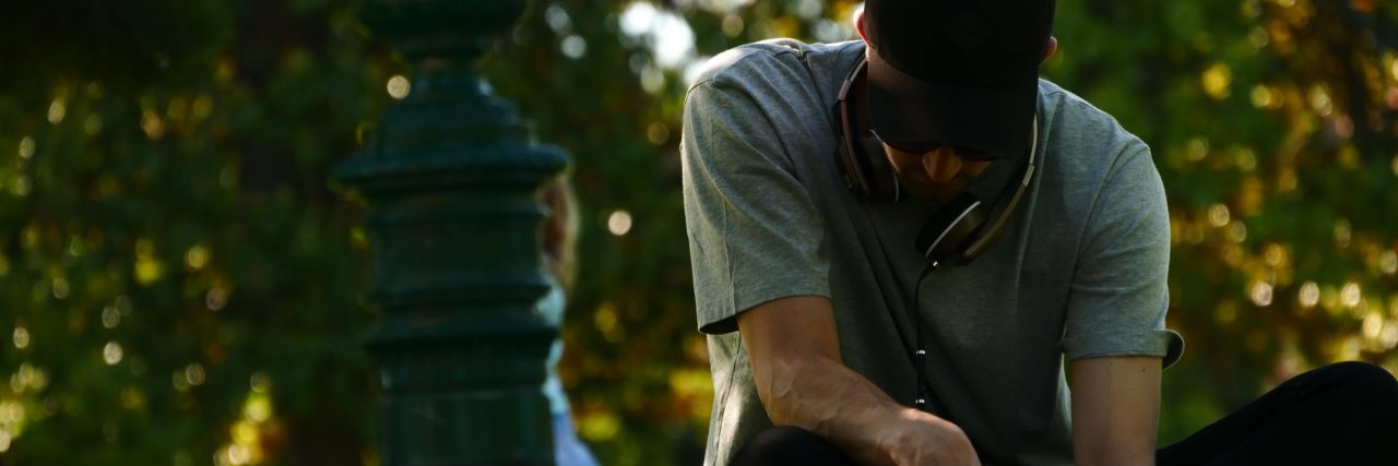 man in park wearing hat writing in book