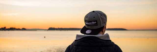 a man stands in front of a sunset