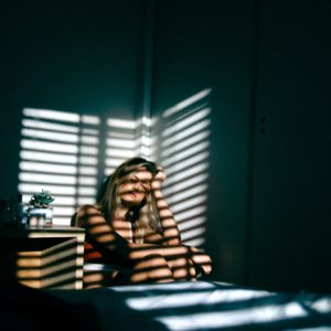 woman sits in the corner of the room with the blinds reflecting off of her