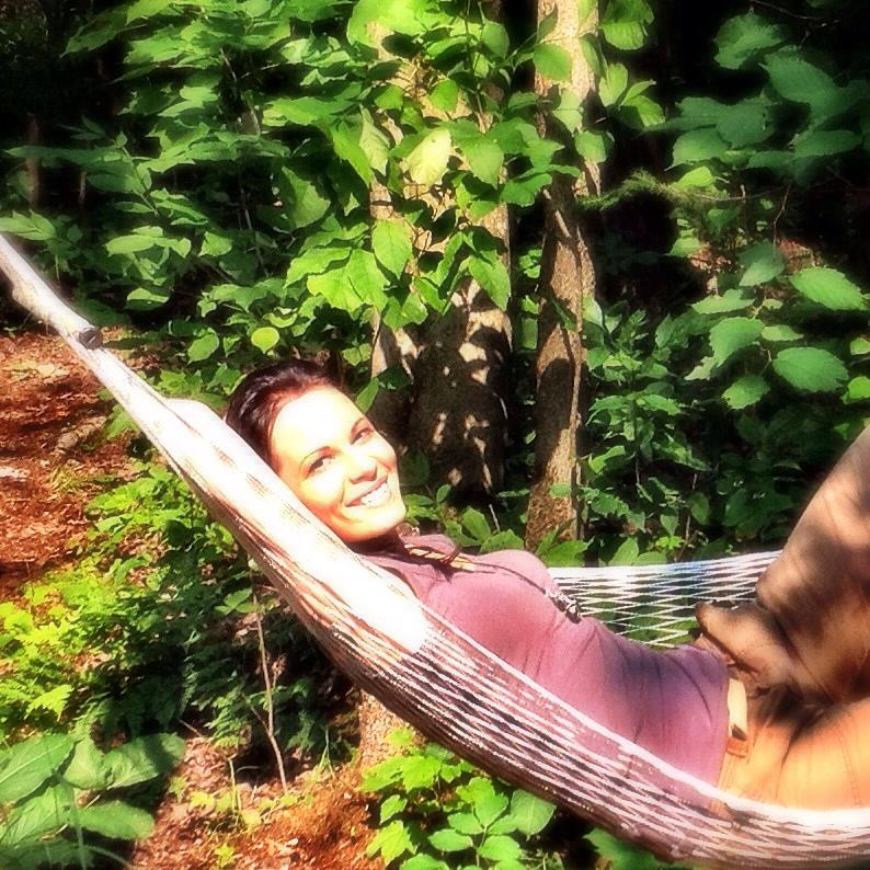 The writer laying in a hammock.