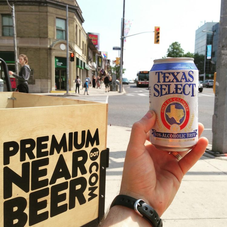 sign that says premium near beer and hand holding can of beer
