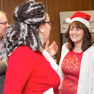 A photo of the writer wearing a Santa hat at a Christmas party.