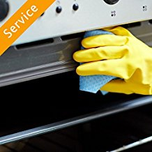 person scrubbing a stove with blue sponge and yellow gloves