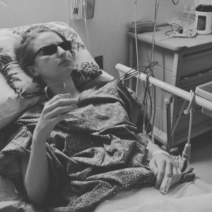 black and white photo of a woman lying in a hospital bed