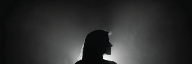 woman stands in dark with light shining behind her