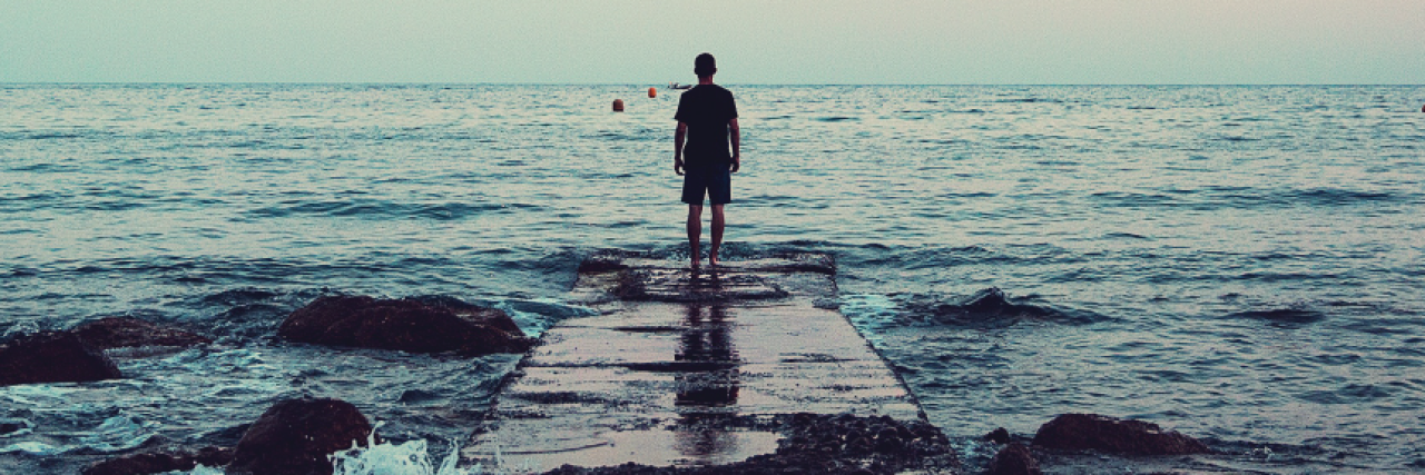 man stands at the end of a dock surrounded by water and the sunset