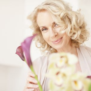An older woman holding flowers.