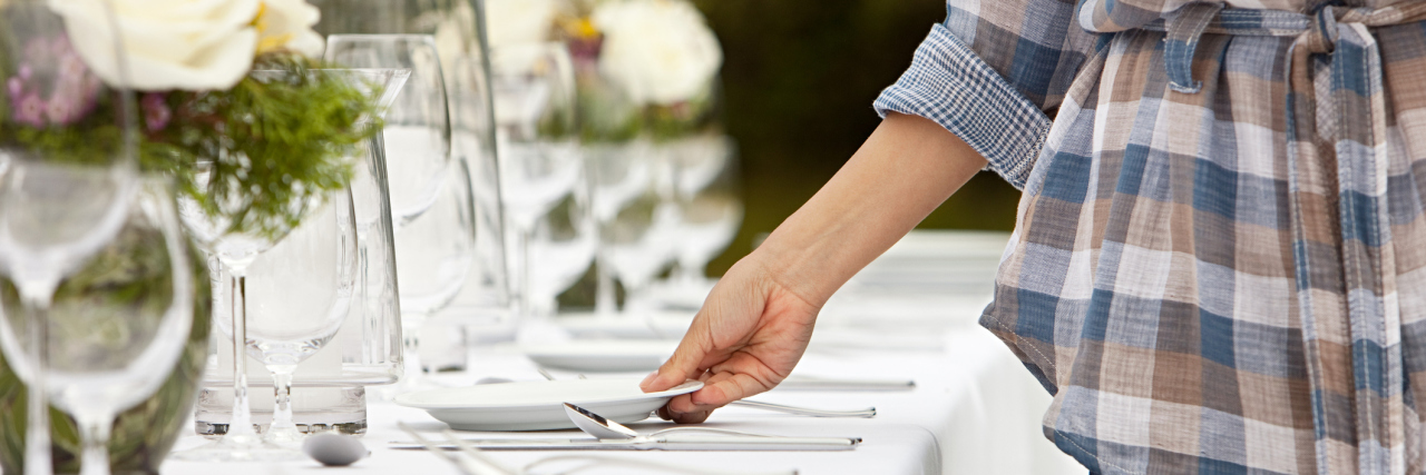 A woman setting a table with plates.