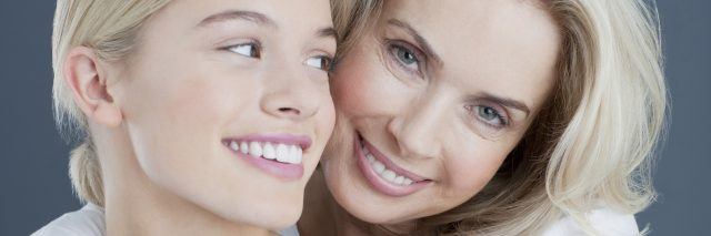 A mother and daughter smiling.
