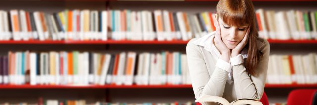 A young woman sitting in a library, reading a book.