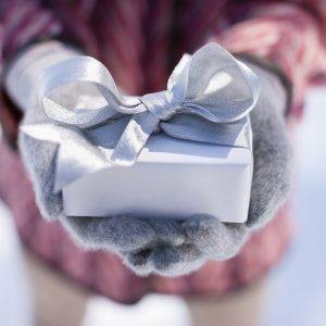 woman wearing gloves outside in the snow and holding a silver wrapped present