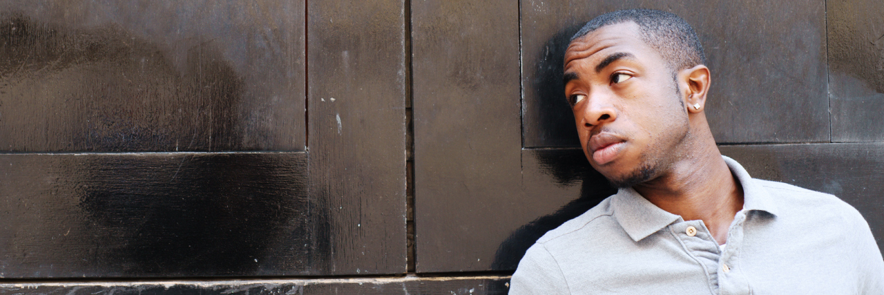 young black man leaning on door looking away from camera