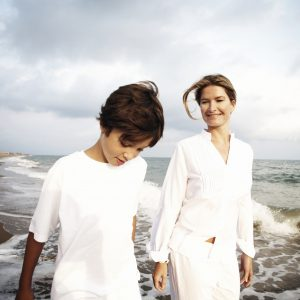 A mother and son walking on the beach.