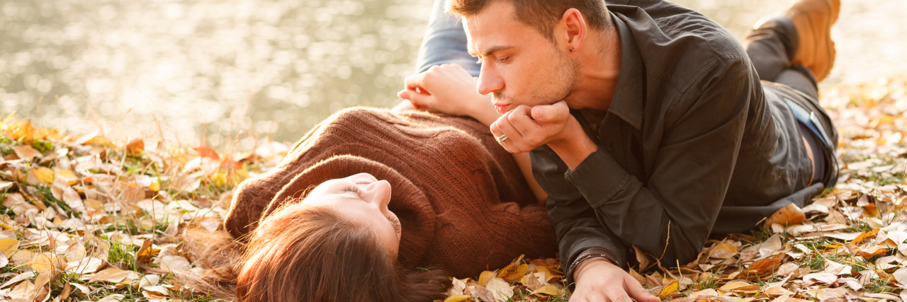young couple lying on autumn leaves by shore of lake