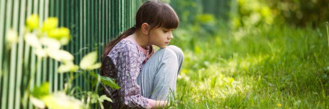 Sad girl sitting on the grass.