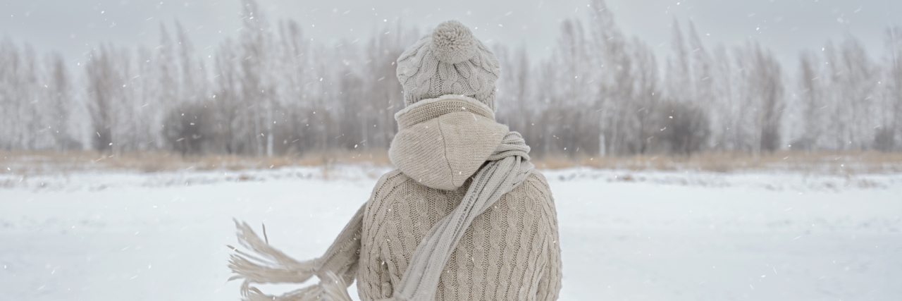 Unrecognizable woman stands back in the woods in winter