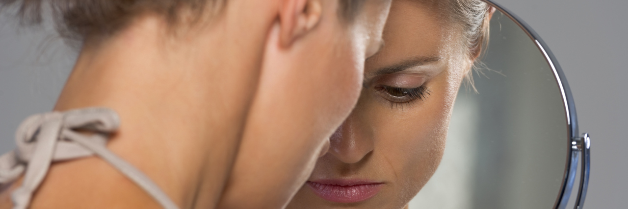 A stressed woman looking at her reflection in the mirror.