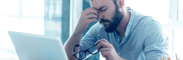 frustrated upset young man with beard in front of laptop pinching bridge of nose