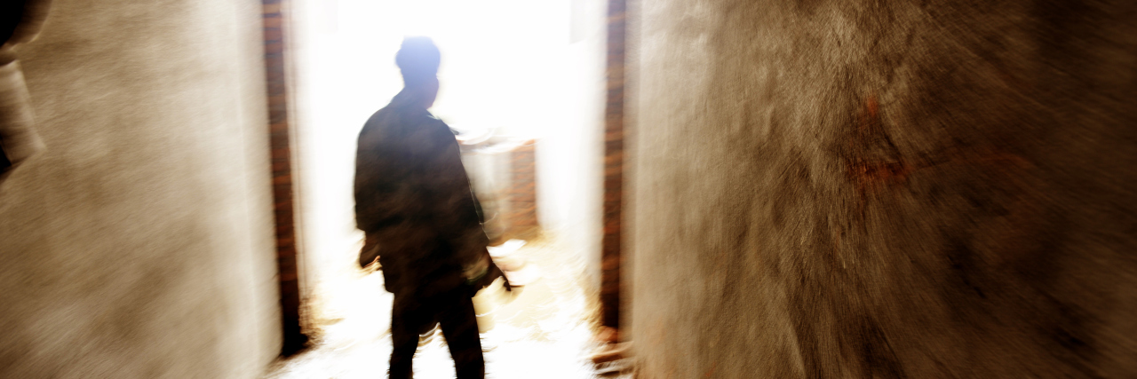 A lonely person standing in a narrow passage
