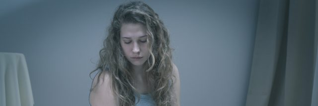 Girl with serious depression sitting in bed