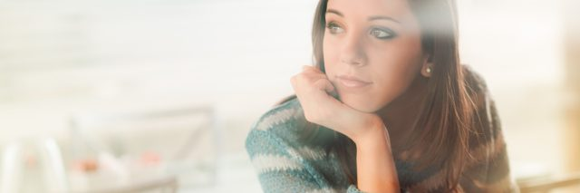 pensive woman sitting in front of laptop with hand on chin